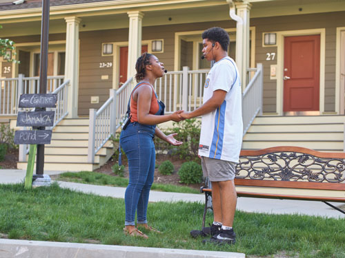 A young woman and young man sing and hold hands facing one another outside on a sunny day. Image by Mark Saperstein.
