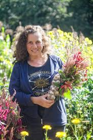 Deb Habib standing in a field of tall grass, holding a bouquet of fresh cut flowers